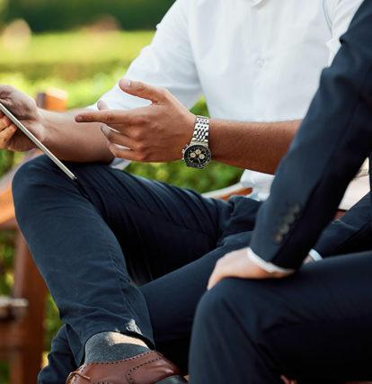 two business men sit on outdoor benches working on tablet